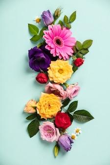 Mise en page créative faite avec de belles fleurs sur fond bleu. lay plat. concept minimal du printemps