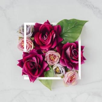 Mise en page créative faite avec des fleurs et un cadre blanc.
