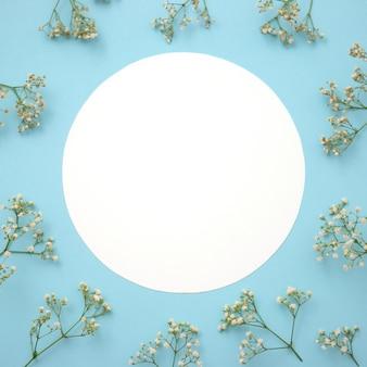Mise en page créative faite de fleurs avec note de carte papier sur fond bleu. lay plat.