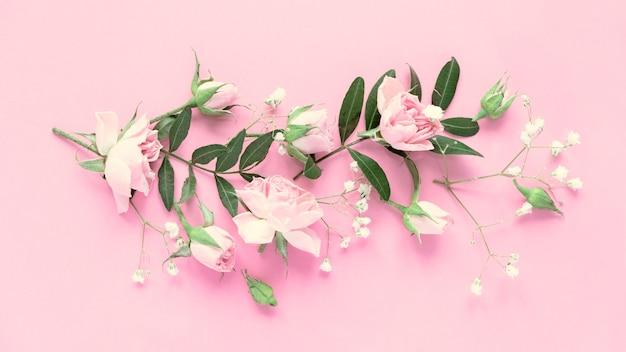 Mise en page créative faite avec des fleurs roses et violettes sur fond rose. mise à plat. concept minimal de printemps.