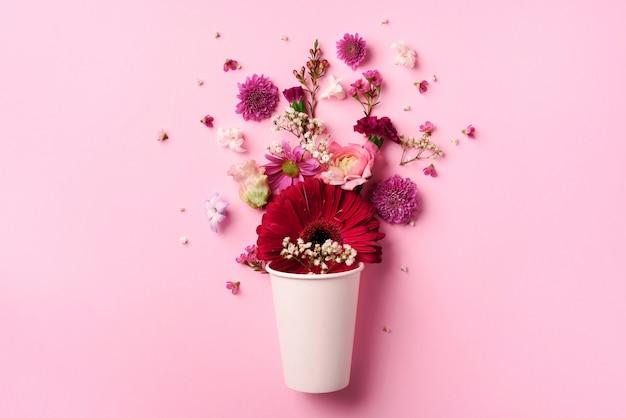 Mise en page créative faite de gobelet en papier blanc avec des fleurs roses.