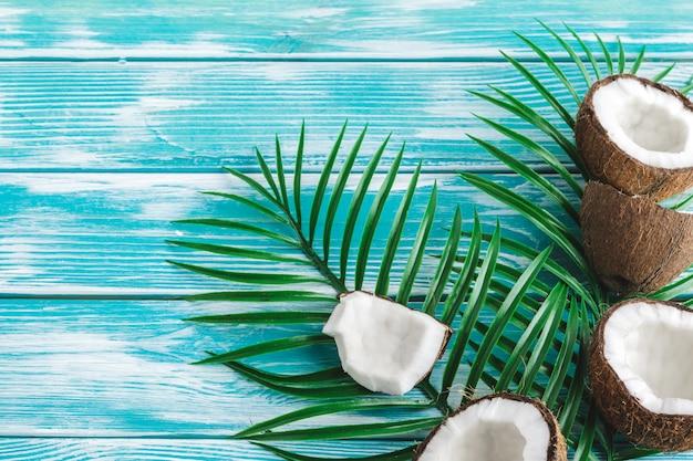 Mise en page créative faite de noix de coco et de feuilles tropicales.