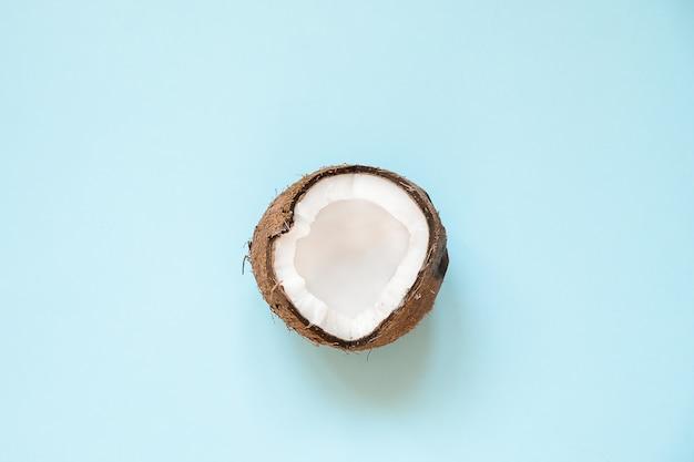 Mise en page créative faite de noix de coco moitié mûre sur bleu