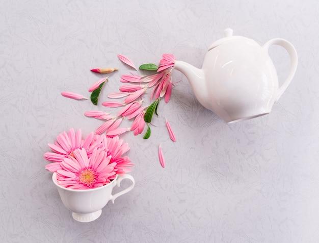Mise en page créative faite de tasse à café et pot avec des fleurs roses sur fond gris.
