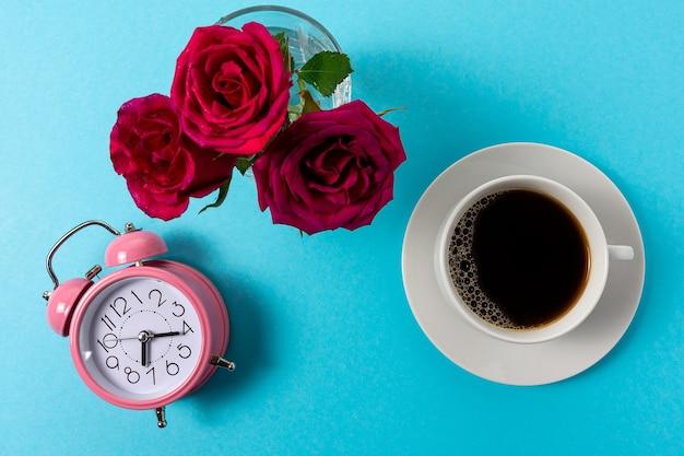 Mise en page créative faite avec une tasse de café et un réveil sur fond bleu.