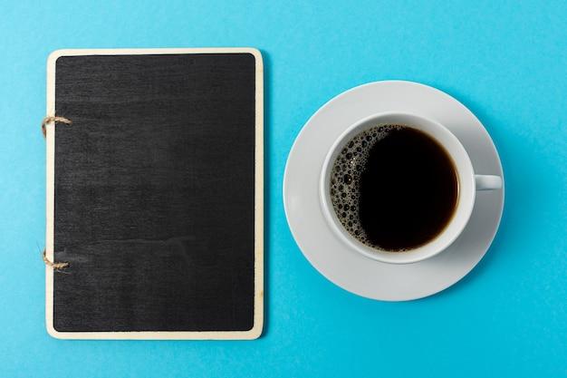 Mise en page créative faite avec une tasse de café et un tableau noir sur fond bleu.