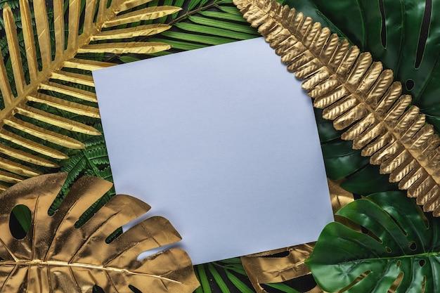 Mise en page créative avec des feuilles de palmier tropical or et vert avec cadre blanc sur fond noir.