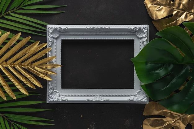 Mise en page créative avec des feuilles de palmier tropical or et vert avec cadre blanc sur scène noire