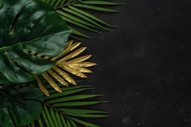 Mise en page créative avec des feuilles de palmier tropical or et vert sur fond noir