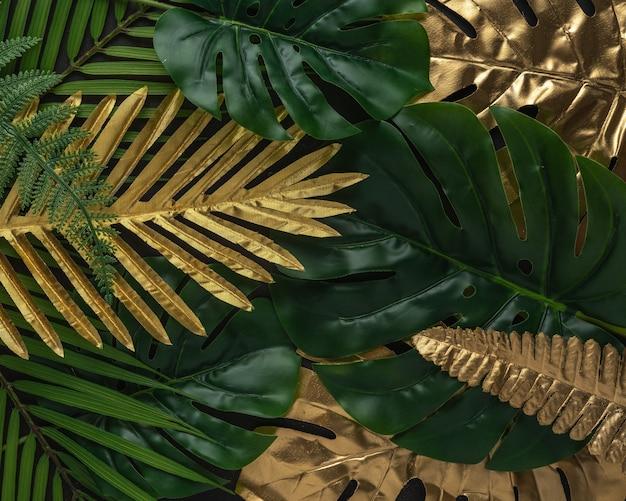 Mise en page créative avec des feuilles de palmier tropical or et vert sur fond noir.