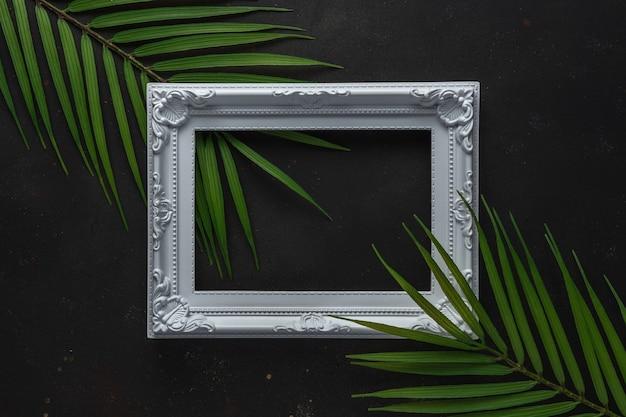 Mise en page créative avec des feuilles de palmiers tropicaux verts avec cadre blanc sur fond noir.