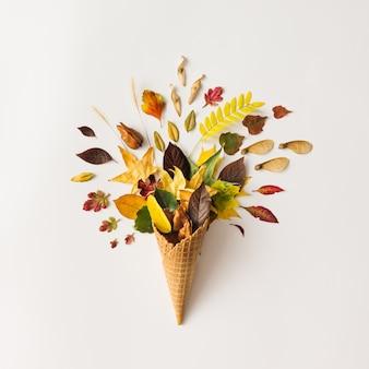 Mise en page créative lumineuse colorée. cornet de crème glacée avec des feuilles d'automne.