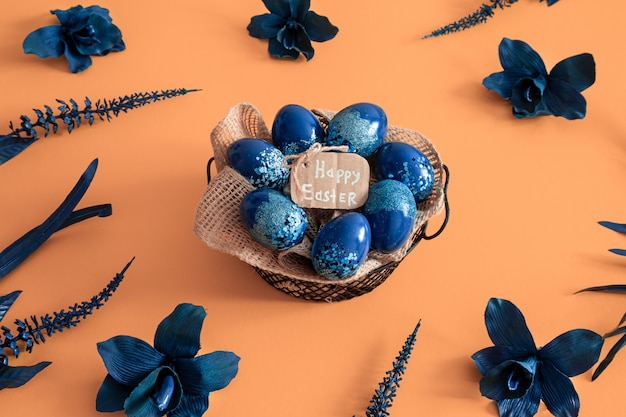 Mise en page créative de pâques faite d'oeufs colorés et de fleurs sur fond bleu.