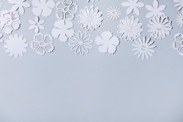 Mise en page créative avec une variété de fleurs en papier blanc sur fond gris. mise à plat, espace de copie