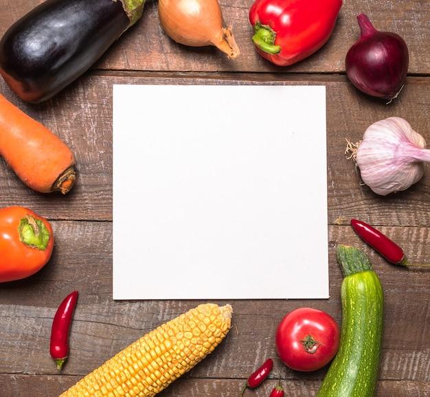 Mise en page avec divers fruits et légumes et carte de papier blanc pour le texte.