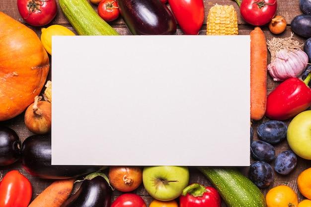 Mise en page avec divers fruits et légumes et carte de papier blanc