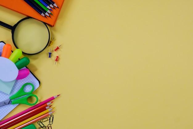 Mise en page avec diverses fournitures scolaires et papeterie sur fond jaune.