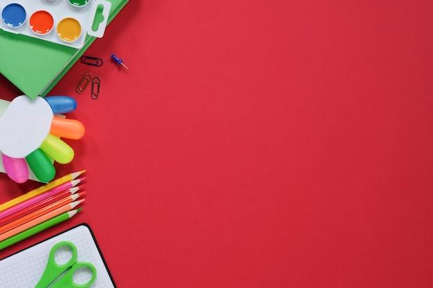 Mise en page avec diverses fournitures scolaires et papeterie sur fond rouge.