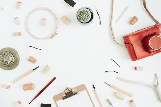 Mise en page avec espace de copie en appareil photo rétro, succulentes, outils pour les arts faits à la main, presse-papiers sur blanc