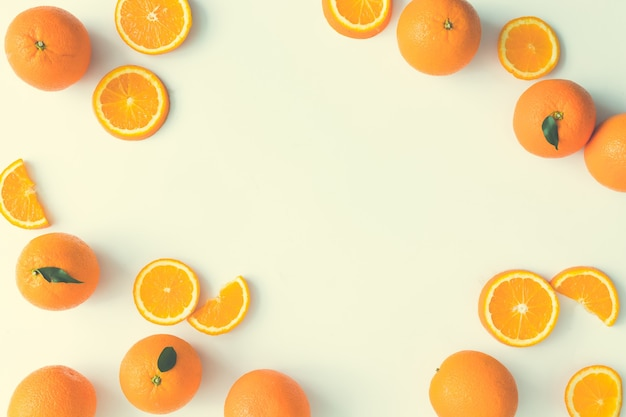 Mise en page d'été créative faite d'oranges et de feuilles vertes sur fond clair. concept minimal de fruits. mise à plat. bordure avec espace de copie.