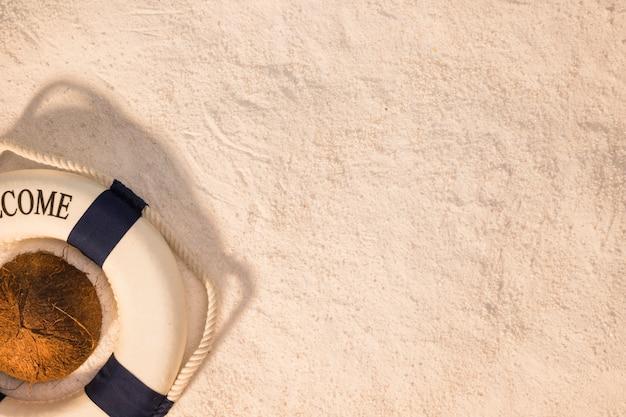Mise en page de l'été de noix de coco et de bouée de sauvetage sur le sable