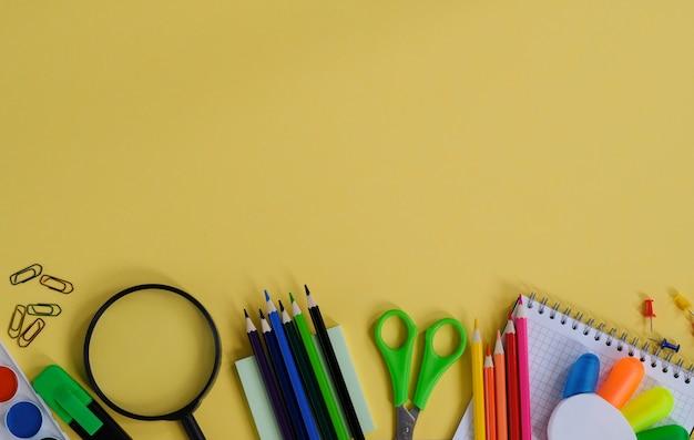 Mise en page avec des fournitures scolaires et de la papeterie sur fond jaune.