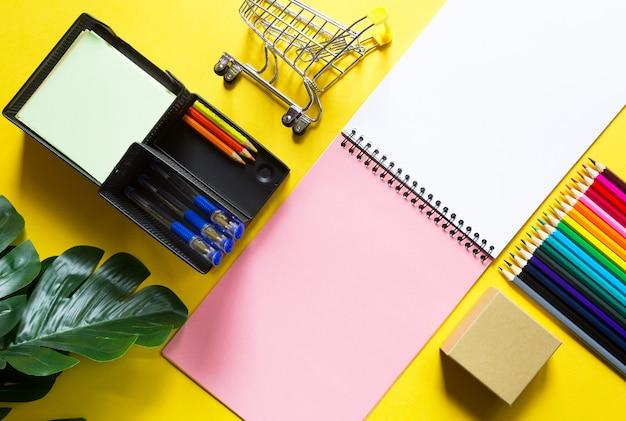 Mise en page de papeterie multicolore sur fond jaune cahier à spirale, crayons de couleur,