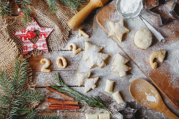 Mise en page à plat sur une table en bois faite de biscuits de noël en forme d'arbres de noël
