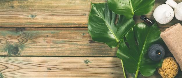 Mise en page plate avec des feuilles de monstera et des produits de soins cosmétiques