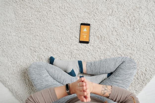 Mise en page plate de la jeune femme aux jambes croisées en gardant les mains jointes par la poitrine tout en méditant sur le sol