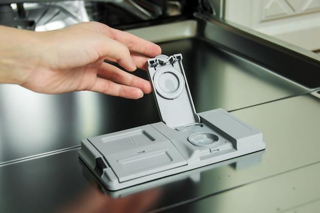 Mise en place du détergent pour lave-vaisselle pour la vaisselle sale.
