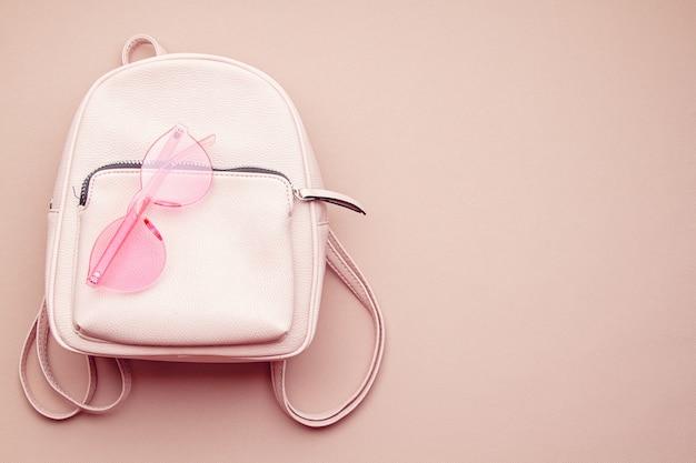 Mise à plat avec accessoires femme rose avec sac à dos et lunettes de soleil