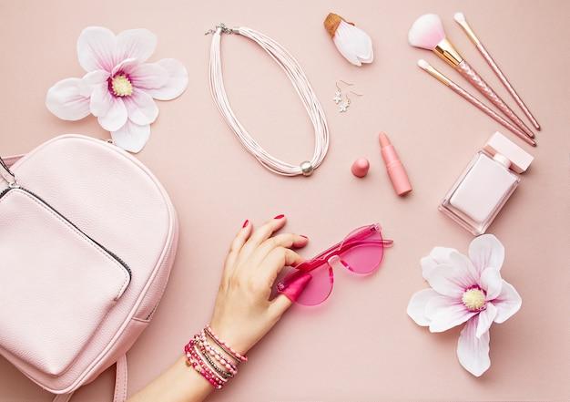 Mise à plat avec accessoires femme rose avec sac à dos et main de femme tenant les lunettes de soleil. tendances mode estivale, idée shopping