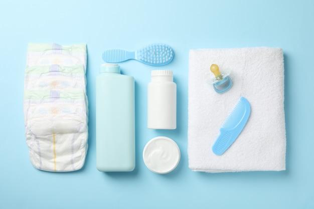 Mise à plat avec des accessoires d'hygiène pour bébé sur le mur bleu