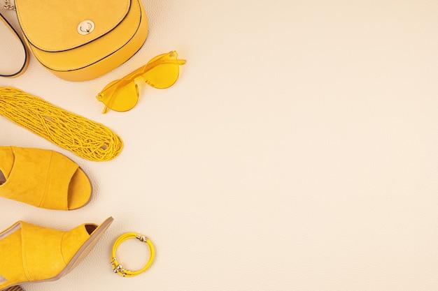 Mise à plat avec des accessoires de mode femme dans les couleurs jaunes et bleus. blog de mode, style d'été, concept de shopping et de tendances