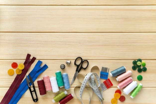 Mise à plat des accessoires pour tailleur. ensemble de fournitures de couture sur fond en bois, espace pour le texte.
