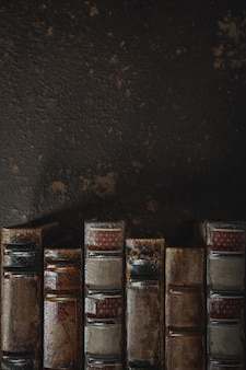 Mise à plat à l'ancienne avec pile de livres reliés en cuir antique contre un mur sombre. littérature, lecture, concept d'éducation. style rétro et vintage. copyspace pour votre annonce. archives antiques.