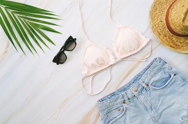 Mise à plat d'articles d'été avec bikini pastel, lunettes de soleil, jeans, chapeau et plante tropicale verte sur fond de marbre, concept de mode et d'été
