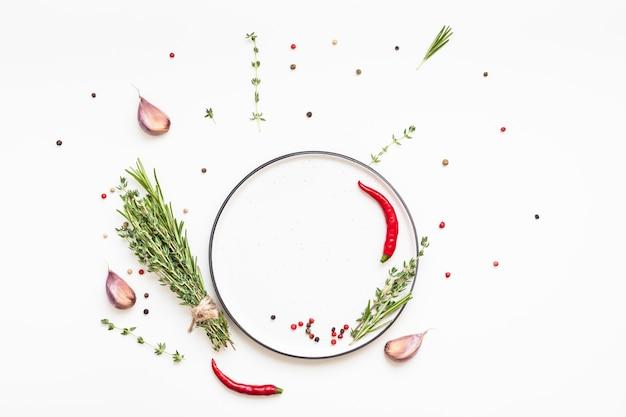 Mise à plat assiette vide maquette espace vide carte d'invitation fond blanc herbes vertes et épices