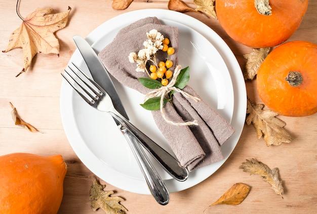 Mise à plat des assiettes pour le dîner de thanksgiving avec des couverts