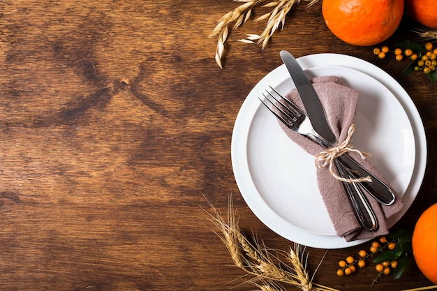 Mise à plat des assiettes pour le dîner de thanksgiving avec espace de copie et couverts