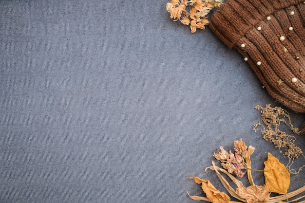 Mise à plat automne-hiver. bonnet tricoté marron et feuilles sèches sur fond blanc bleu.