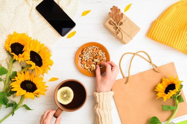 Mise à plat d'automne avec des mains féminines tenant une noix et une tasse de thé à la maison confortable