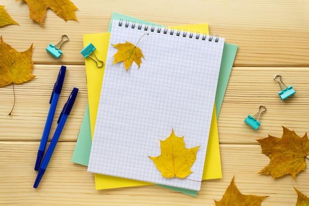 Mise à plat d'automne de papeterie scolaire ou de bureau sur un fond en bois clair.