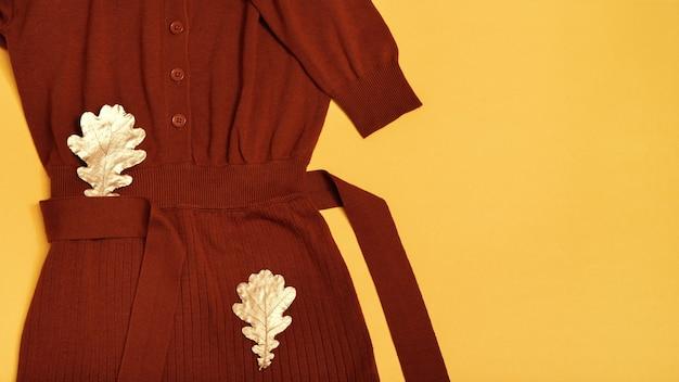 Mise à plat d'automne avec robe en laine tricotée de couleur terre cuite, feuilles sèches dorées