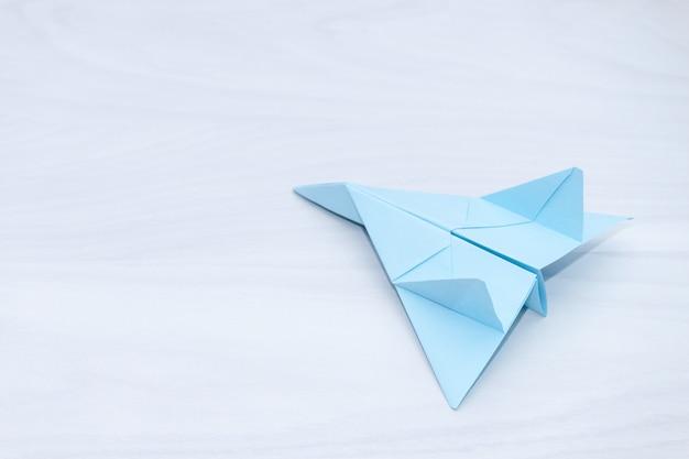Mise à plat d'avion en papier bleu sur fond de bois blanc.