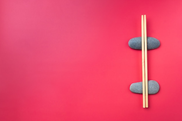 Mise à plat. des baguettes en bois clair reposent sur des pierres ovales sur fond rose. couverts traditionnels asiatiques. copier l'espace
