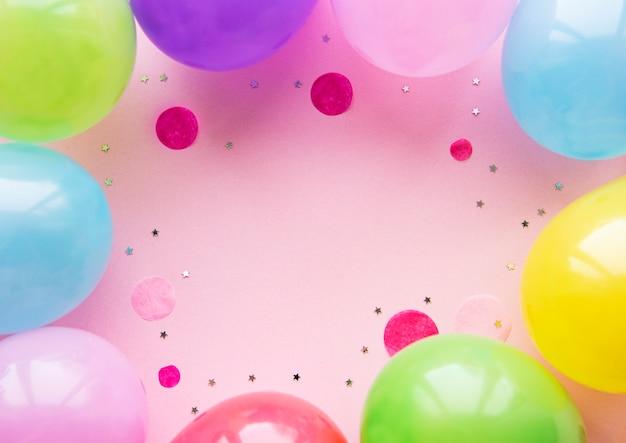 Mise à plat avec des ballons d'anniversaire, des confettis et des rubans sur rose