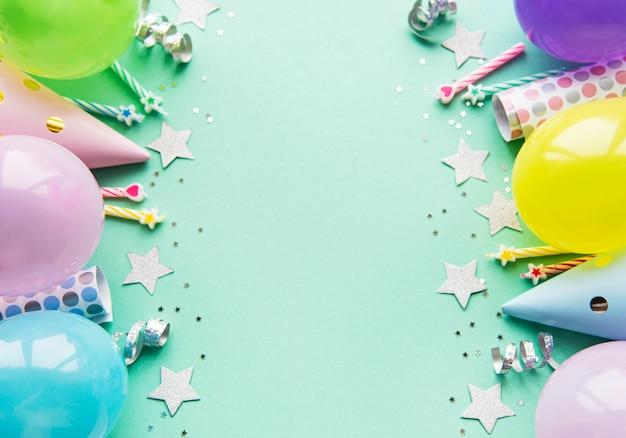 Mise à plat avec des ballons d'anniversaire, des confettis et des rubans sur vert pastel