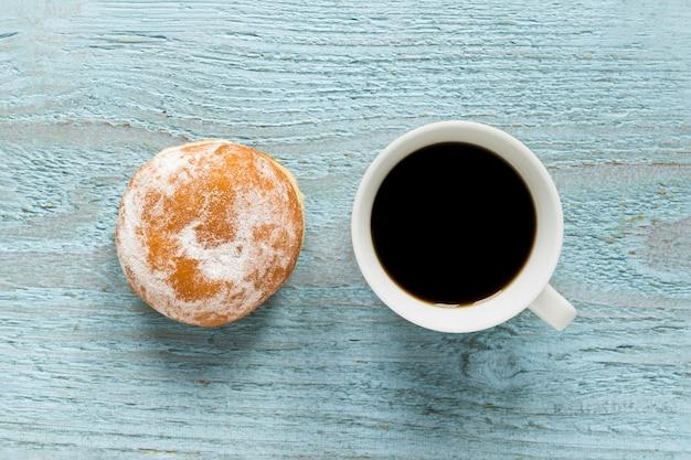 Mise à plat de beignet avec du café sur une surface en bois